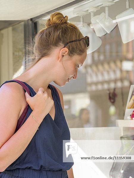 Junge Frau schaut ins Schaufenster