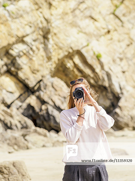 Woman standing at the beach  taking a picture with camera