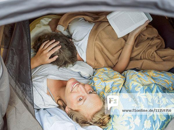 Junges Paar beim Aufwachen im Zelt