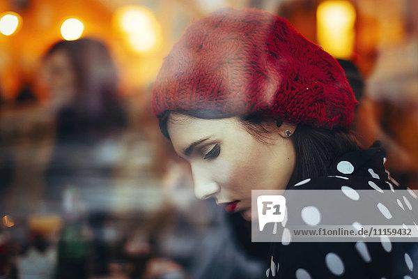 Porträt einer jungen Frau mit rotem Hut hinter der Fensterscheibe einer Kneipe am Abend
