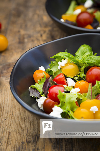 Bowl of leaf salad with goat cream cheese and tomatoes on wood
