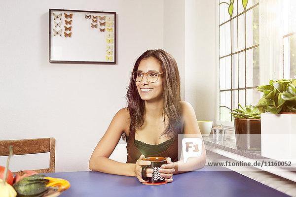 Lächelnde Frau bei Tisch mit Becher
