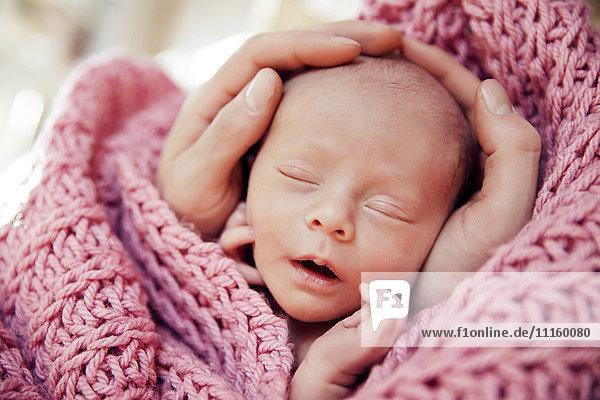 Hände halten den Kopf eines Neugeborenen in einer rosa Wolldecke.