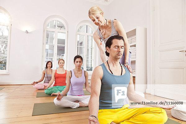 Gruppe von Leuten im Yogastudio,  die in Lotus-Pose sitzen,  während der Instruktor ihren Rücken gerade hält.