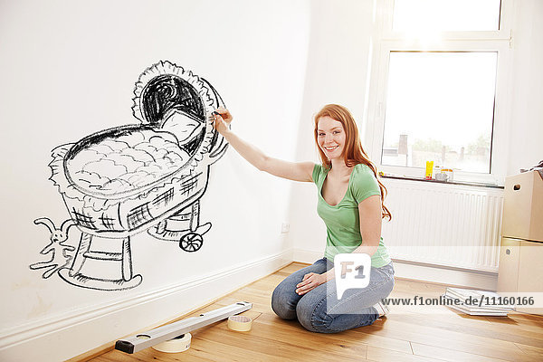 Junge Frau beim Zeichnen eines Babybettes an der Wand in der neuen Wohnung Junge Frau beim Zeichnen eines Babybettes an der Wand in der neuen Wohnung
