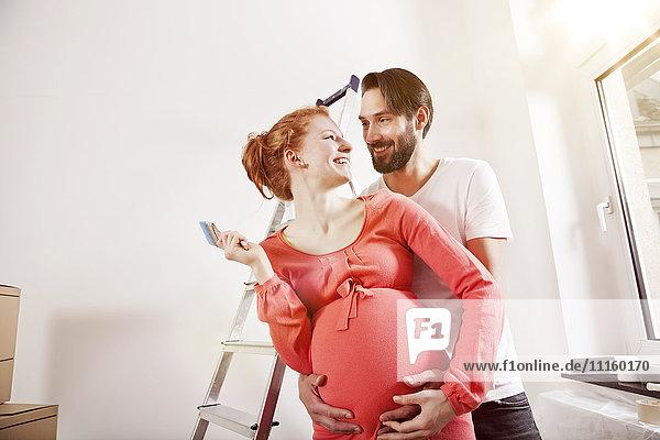 Glücklicher Mann umarmt schwangere Frau beim Renovieren des neuen Hauses Glücklicher Mann umarmt schwangere Frau beim Renovieren des neuen Hauses