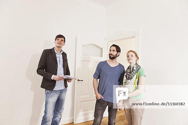 Immobilienmakler zeigt ein Paar in einer neuen Wohnung