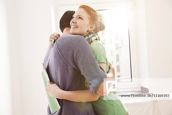 Glückliches junges Paar  das sich am Fenster umarmt.