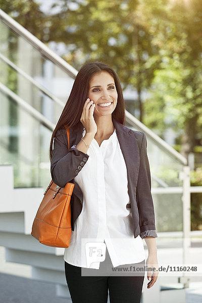 Lächelnde Frau auf dem Handy im Freien