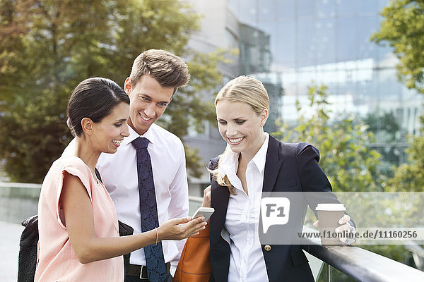 Smiling businesswoman showing cell phone to colleagues