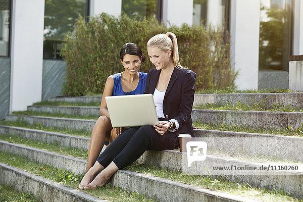 Zwei Geschäftsfrauen sitzen draußen auf einer Treppe mit einem Laptop