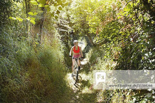 Junge Frau auf dem Mountainbike auf einem Trail