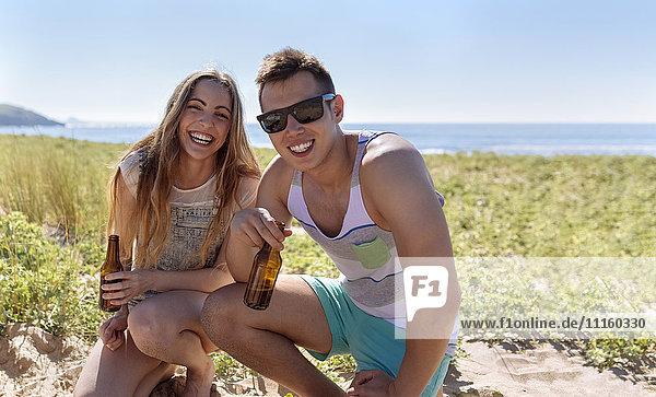 Glückliche Freunde mit Bierflaschen am Strand