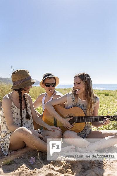 Fröhliches Teenagermädchen beim Gitarrespielen für ihre Freunde am Strand