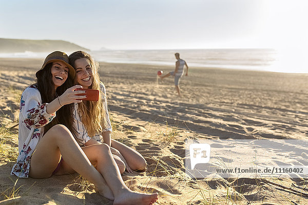 Two best friends sitting on the beach taking selfie with smartphone