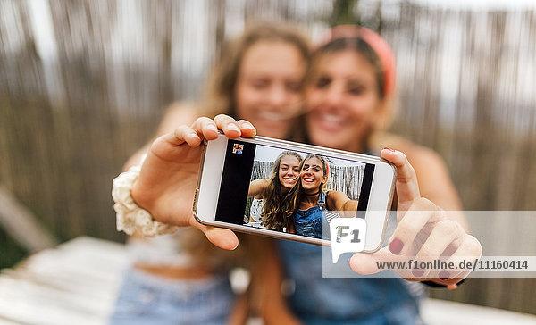 Selfie von zwei lächelnden Teenager-Mädchen auf dem Display des Smartphones