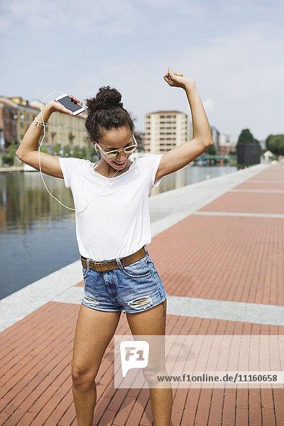 Fröhliche junge Frau beim Musikhören und Tanzen am Flussufer