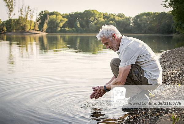 Senior man refreshing at a lake