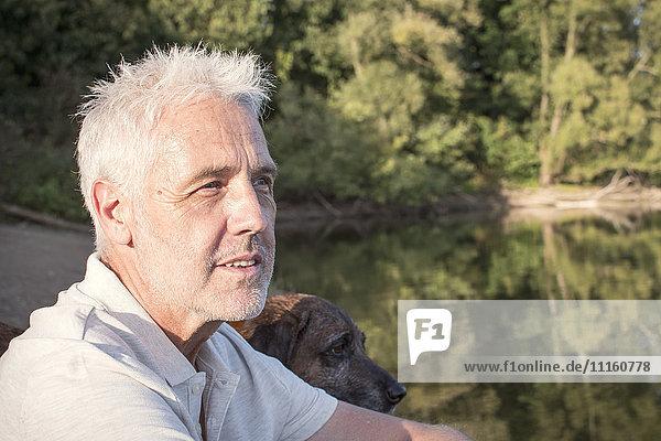Senior man with dog at a lake