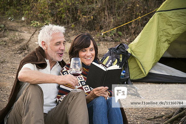 Happy senior couple with wine and book at a tent