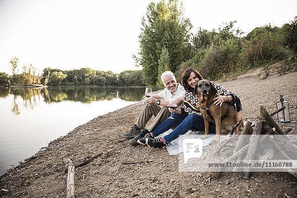 Glückliches Seniorenpaar mit Hund am See am Abend