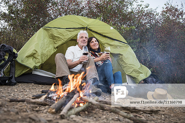 Happy senior couple sitting at campfire with wine at a tent