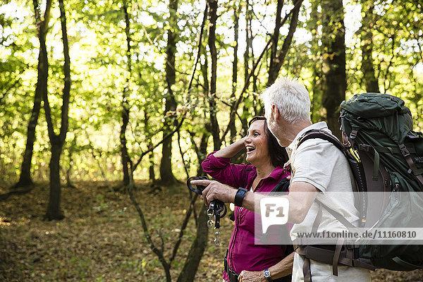 Glückliches Seniorenpaar beim Wandern im Wald
