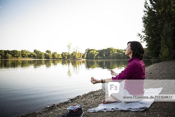 Senior woman at a lake practicing yoga
