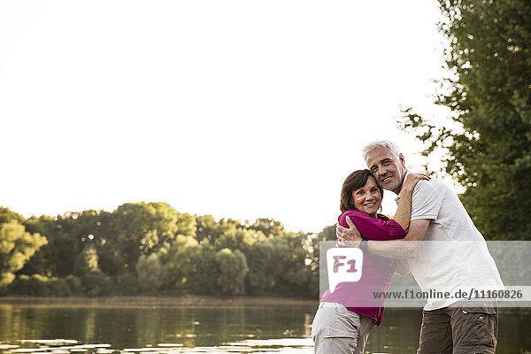 Smiling senior couple embracing at a lake