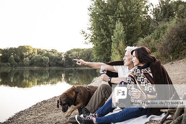 Seniorenpaar mit Hund am See am Abend