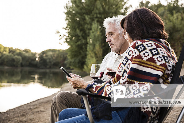 Senior couple with wine sitting at a lake with tablet