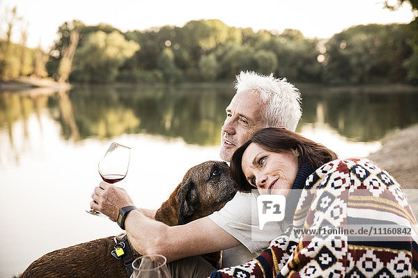 Relaxed senior couple with dog and wine at a lake