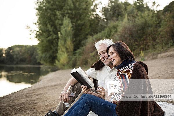 Glückliches Seniorenpaar mit Wein und Buch am See