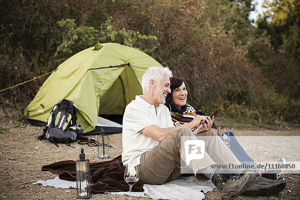 Happy senior couple with cell phone at a tent