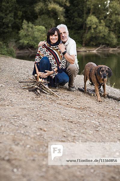 Senior couple with dog at campfire at a lake