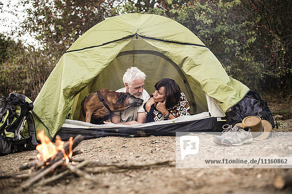 Senior couple with dog lying in tent at campfire