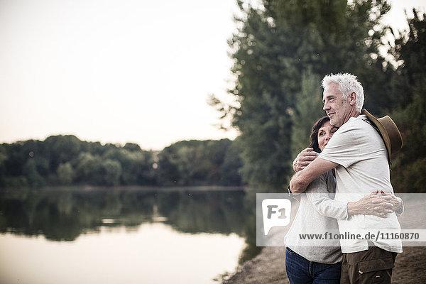 Senior couple embracing at a lake