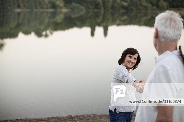 Glückliches Seniorenpaar Hand in Hand an einem See
