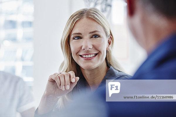 Lächelnde Geschäftsfrau in einem Meeting mit Blick auf Kollegen