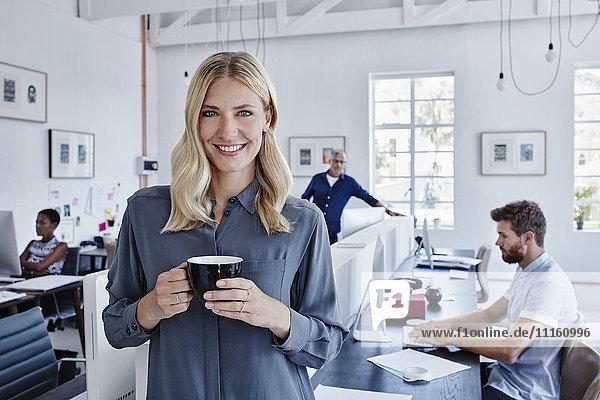 Porträt einer lächelnden Geschäftsfrau im Büro mit Mitarbeitern im Hintergrund