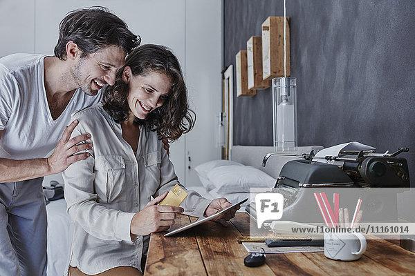 Lächelndes Paar beim Online-Shopping im Schlafzimmer