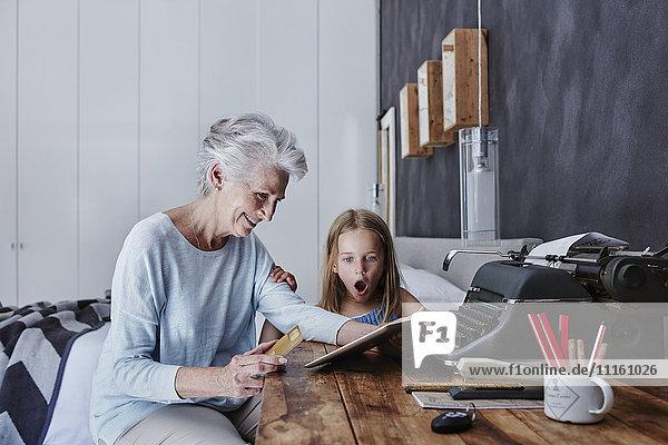 Großmutter und verblüffte Enkelin beim Online-Shopping zu Hause