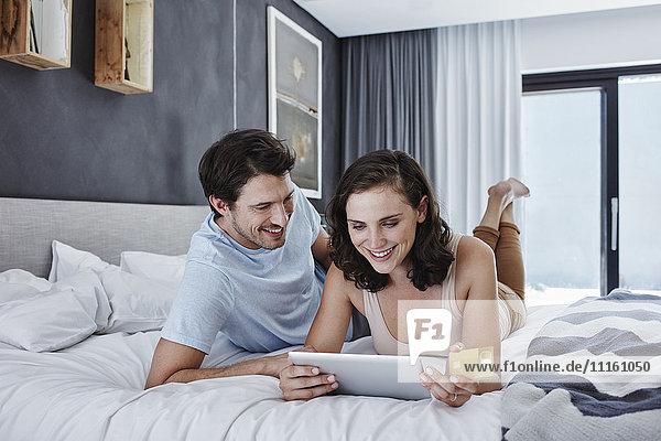 Lächelndes Paar auf dem Bett liegend online einkaufen