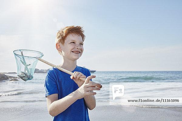 Junge mit Dip-Netz am Meer