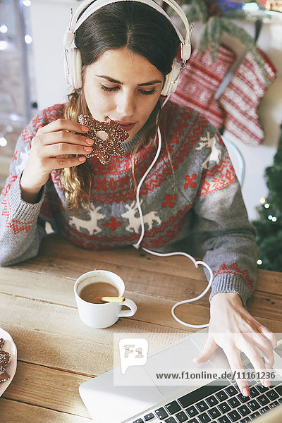 Frau mit Kopfhörer mit Laptop beim Essen Weihnachtsplätzchen