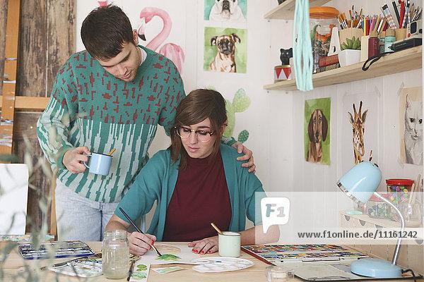Künstlerin malt in ihrem Atelier  während ihr Freund sie beobachtet.