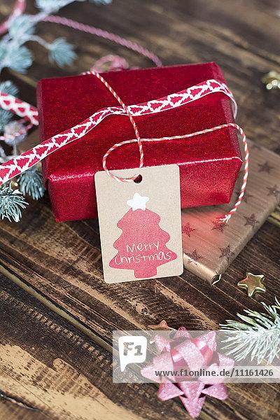 Weihnachtsdekoration und verpackte Geschenke auf Holz