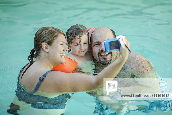 Family taking selfie in swimming pool