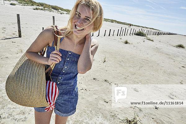 Lachende junge Frau am Strand