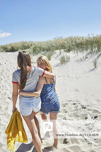 Zwei Freundinnen gehen Arm in Arm am Strand.